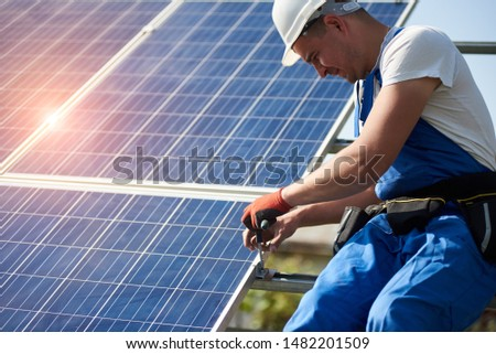 Professional technician connecting solar photo voltaic panel to metal platform using screwdriver. Stand-alone solar panel system installation, efficiency and professionalism concept. #1482201509