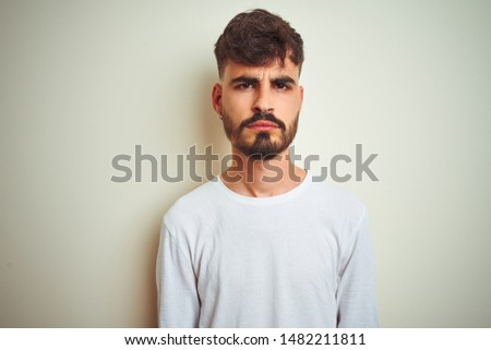 Young man with tattoo wearing t-shirt standing over isolated white background skeptic and nervous, frowning upset because of problem. Negative person. #1482211811