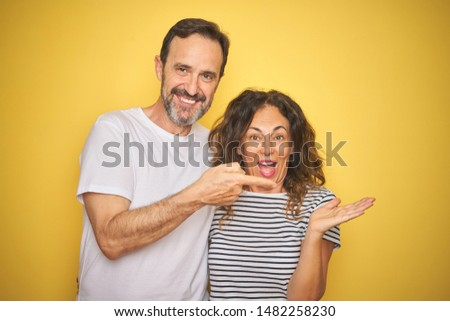 Beautiful middle age couple together standing over isolated yellow background very happy pointing with hand and finger #1482258230