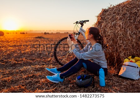 Young bicyclist having rest after a ride in autumn field at sunset. Woman taking picture using phone by haystack