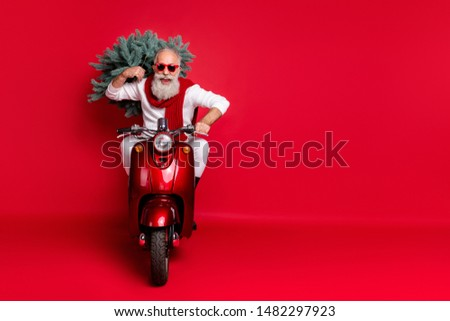 Full length photo of cheerful hipster carry fir tree having eyewear eyeglasses drive bike wearing white sweater trousers pants isolated over red background #1482297923