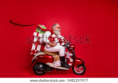 Profile side view of his he nice attractive stylish cheerful cheery gray-haired man riding driving bike delivering shop sale discount boxes isolated over bright vivid shine red background #1482297977