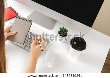 Woman making notes in notepad in an office #1482310241