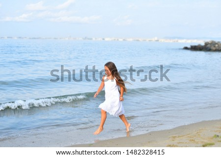 Beautiful young girl running on the beach barefoot in the water. Beautiful girl legs in the water. #1482328415