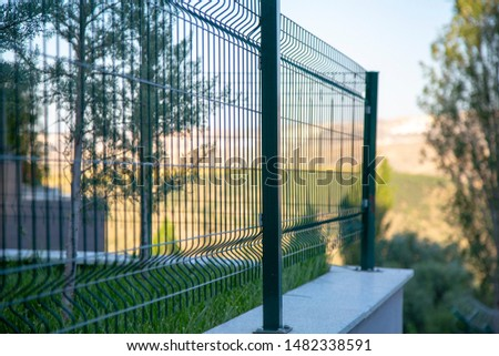 Steel grating fence of soccer field,Metal fence wire with bokeh in the background . Coiled razor wire with its sharp steel barbs on top of a wire mesh perimeter fence ensuring safety and security. #1482338591