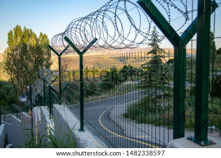 Steel grating fence of soccer field,Metal fence wire with bokeh in the background . Coiled razor wire with its sharp steel barbs on top of a wire mesh perimeter fence ensuring safety and security. #1482338597
