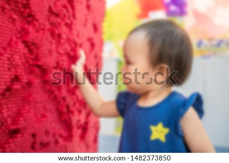 Blur of little cute girl playing red pin art board. Concept of play development.