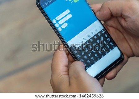 Person receiving and sending encrypted messages on a mobile phone. Alien message concept. #1482459626