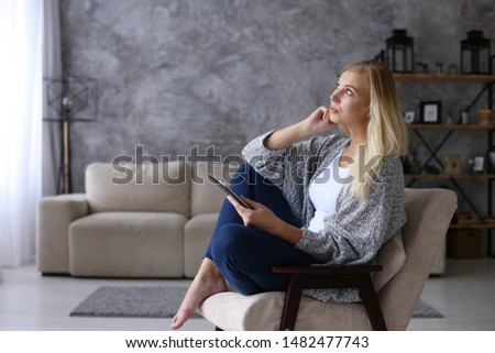 A girl sits in chair in the morning and reads a tablet. Comfortably working remotely at home. Copy space. #1482477743