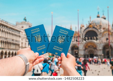 hand holding ukrainian biometric passports travel concept freedom of movement italy venice