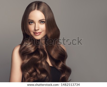 Beauty girl with long  and   shiny wavy hair .  Beautiful   woman model with curly hairstyle . Royalty-Free Stock Photo #1482513734