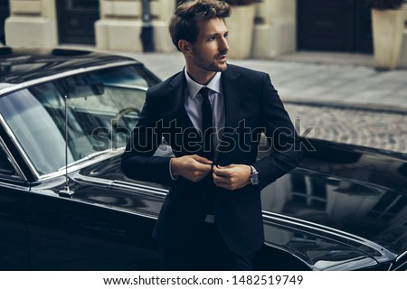Handsome man in black suit with old classic car Royalty-Free Stock Photo #1482519749