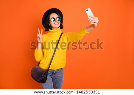 Photo of photographing girl wearing headwear cap blogging with her new phone in yellow sweater showing v-sign symbol isolated with orange background