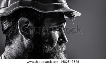 Worker in hardhat. Portrait mechanical worker. Bearded man in suit with construction helmet. Portrait of handsome engineer. Builder in hard hat, foreman or repairman in the helmet. Black and white. #1482547826