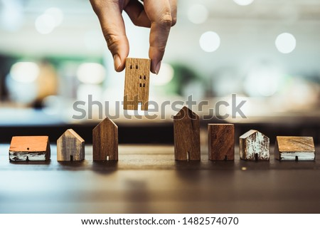 Hand choosing mini wood house model from model and row of coin money on wood table, selective focus, Planning to buy property. Choose what's the best. A symbol for construction ,ecology, loan concepts #1482574070
