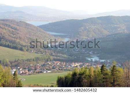 A view of a forest, the Soła river, the Międzybrodzkie lake and a city in the valley in the mountain range of Little Beskids in southern Poland #1482605432