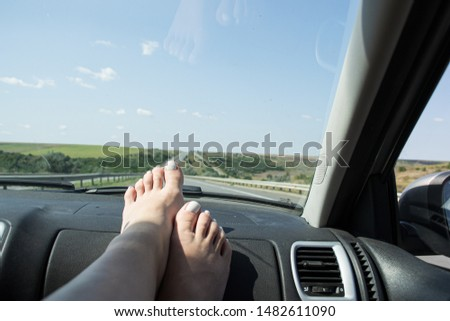 Legs of a girl in a car near the glass #1482611090