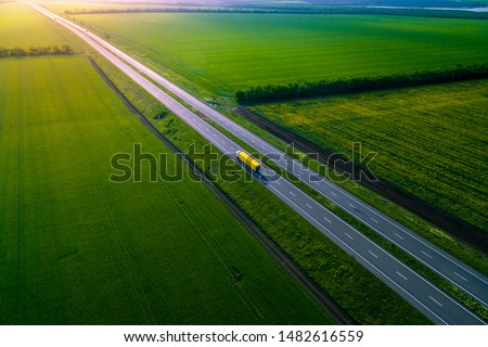 yellow truck driving on asphalt road along the green fields. seen from the air. Aerial view landscape. drone photography.  cargo delivery Left side traffic #1482616559