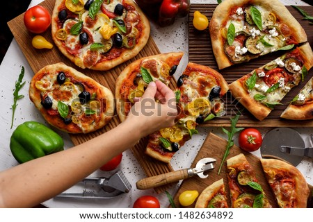 Woman hand putting basil leaves on pizzas. Homemade Italian style pizzas with olives, eggplants, bell peppers, tomatoes and basil on white background top view #1482634892
