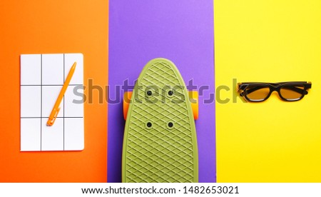 White notebook with orange pen,skateboard and glasses on orange,purple and yellow background.