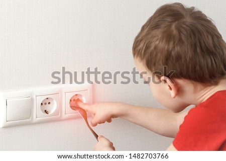 Toddler touches a power outlet. Dangerous children games at home with electricity. Royalty-Free Stock Photo #1482703766