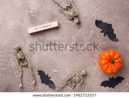 Halloween background with skeletons, pumpkin and bat