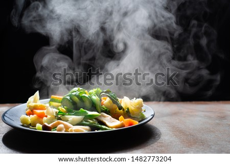 The steam from the vegetables carrot broccoli cauliflower on dish , a steaming. Boiled hot Healthy food on table on black background,hot food and healthy meal concept #1482773204