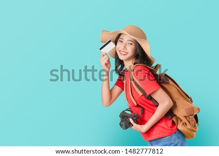 Cheerful Asian woman holding credit card ready to travel, tourism and vacation with backpack, photo camera on blue background.