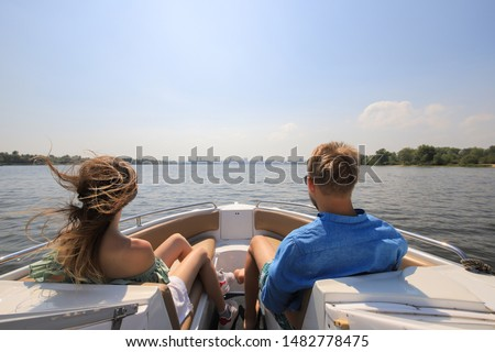 Young couple boating on a motor boat. Boy with girl on the boat enjoy cruise trip. #1482778475