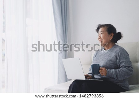 Happy Elderly woman using laptop in living room at home. #1482793856