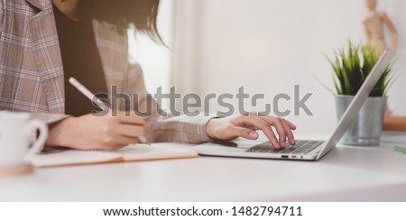 Motivated young businesswoman planing her strategy while typing on laptop and writing on notebook  Royalty-Free Stock Photo #1482794711