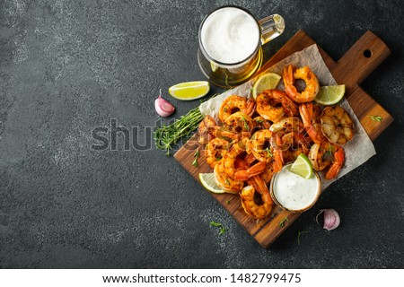 Grilled shrimps or prawns served with lime, garlic and white sauce on a dark concrete background. Seafood. Top view with copy space. Flat lay #1482799475