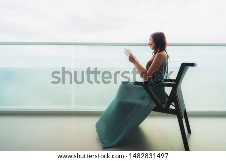 Beautiful portrait young asian woman  reading book at outdoor balcony with sea ocean view background #1482831497
