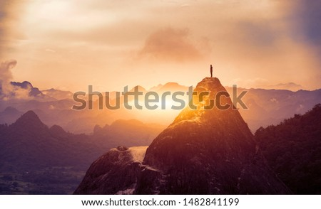 Peak Panoramic view on foggy mountains hills Successfully achieving your goal, Silhouette male on the mountain. Success Business Leadership, Winner Man on top. Business Sport and active life concept Royalty-Free Stock Photo #1482841199