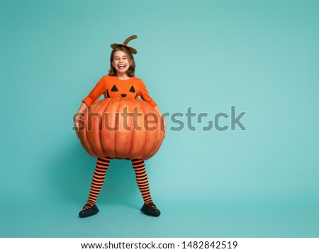 Happy Halloween! Cute little girl in pumpkin costume on turquoise background. Royalty-Free Stock Photo #1482842519