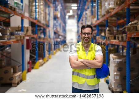 Portrait of middle aged caucasian warehouse worker standing in large warehouse distribution center with arms crossed. In background shelves with goods. Worker smilling and looking to the camera. #1482857198
