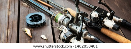 Fishing rods and reels on wooden background #1482858401