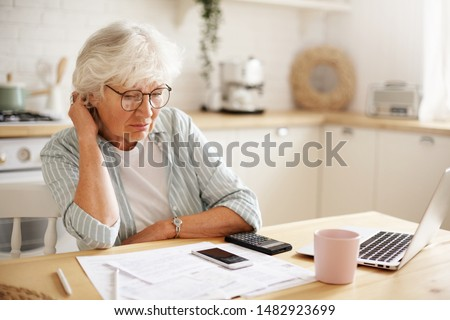 People, age, technology and finances. Depressed unhappy retired woman paying domestic bills online, trying hard to make both ends meet, sitting at kitchen table, surrounded with papers, using gadgets #1482923699