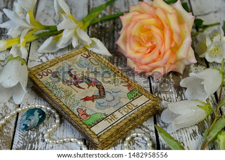 Tarot cards and flowers on witch wooden altar. Esoteric, gothic and occult concept, Halloween mystic background, divination ritual