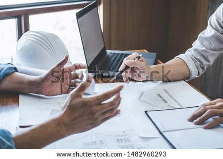 Construction and structure concept of Engineer or architect meeting for project working with partner and engineering tools on model building and blueprint in working site, contract for both companies. #1482960293