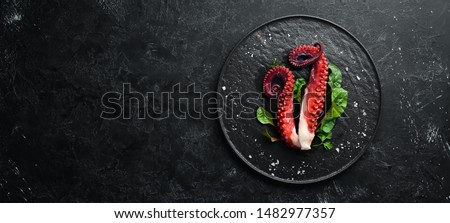 Boiled octopus tentacles on a stone plate. Seafood. Top view. Free copy space. #1482977357