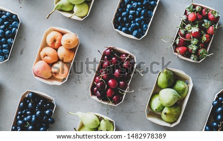 Summer fruit and berry assortment. Flat-lay of fresh strawberries, cherries, grapes, blueberries, pears, apricots, figs in eco-friendly boxes over grey background, top view. Local farmers produce #1482978389