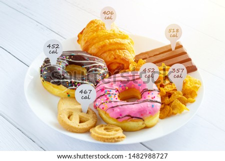 Calories counting and food control concept. doughnut ,croissant ,chocolate and cookies with label of quantity of calories for Calories measuring #1482988727