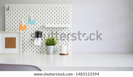 Workspace office supply and pegboard on white table copy space. #1483123394