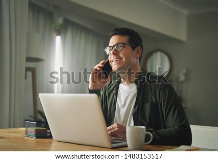 Man talking on a mobile phone and working on his laptop #1483153517