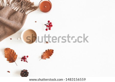 Autumn composition. Cup of coffee, scarf, dried leaves, flowers, rowan berries on white background. Autumn, fall, thanksgiving day concept. Flat lay, top view, copy space #1483156559