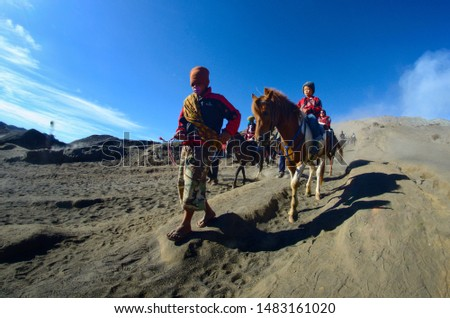 Bromo,  East Java, Indonesia, June 17, 2015- Tourists enjoy the beauty of Mount Bromo with a tour guide using a horse.  #1483161020
