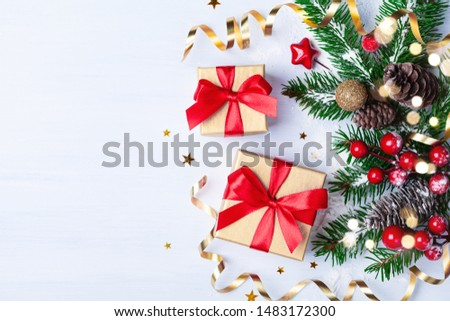 Two golden gift or present boxes, snowy fir branches, conifer cones, Christmas decoration and red berry on white table top view #1483172300