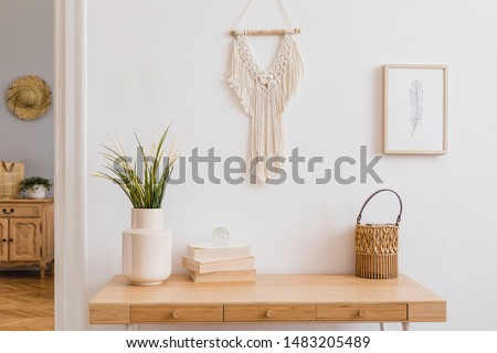 Stylish and modern boho interior of living room with mock up photo frames, flowers in vase, wooden desk, beige macrame and elegant accessories. Design home decor. Bohemian concept. Mockup ready to use #1483205489