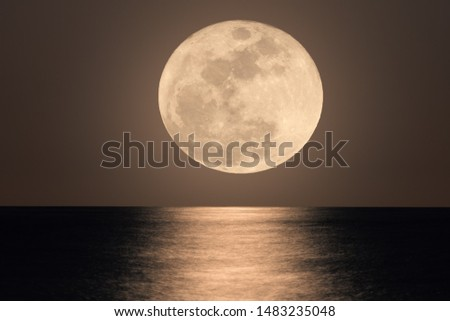 The full moon in close up by zoom. Illuminated a little longer, the water is soft and finely drawn. The moon and the reflections dominate the picture.